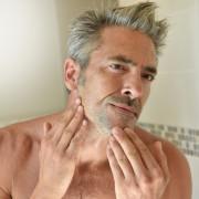 Mature man in bathroom checking beard